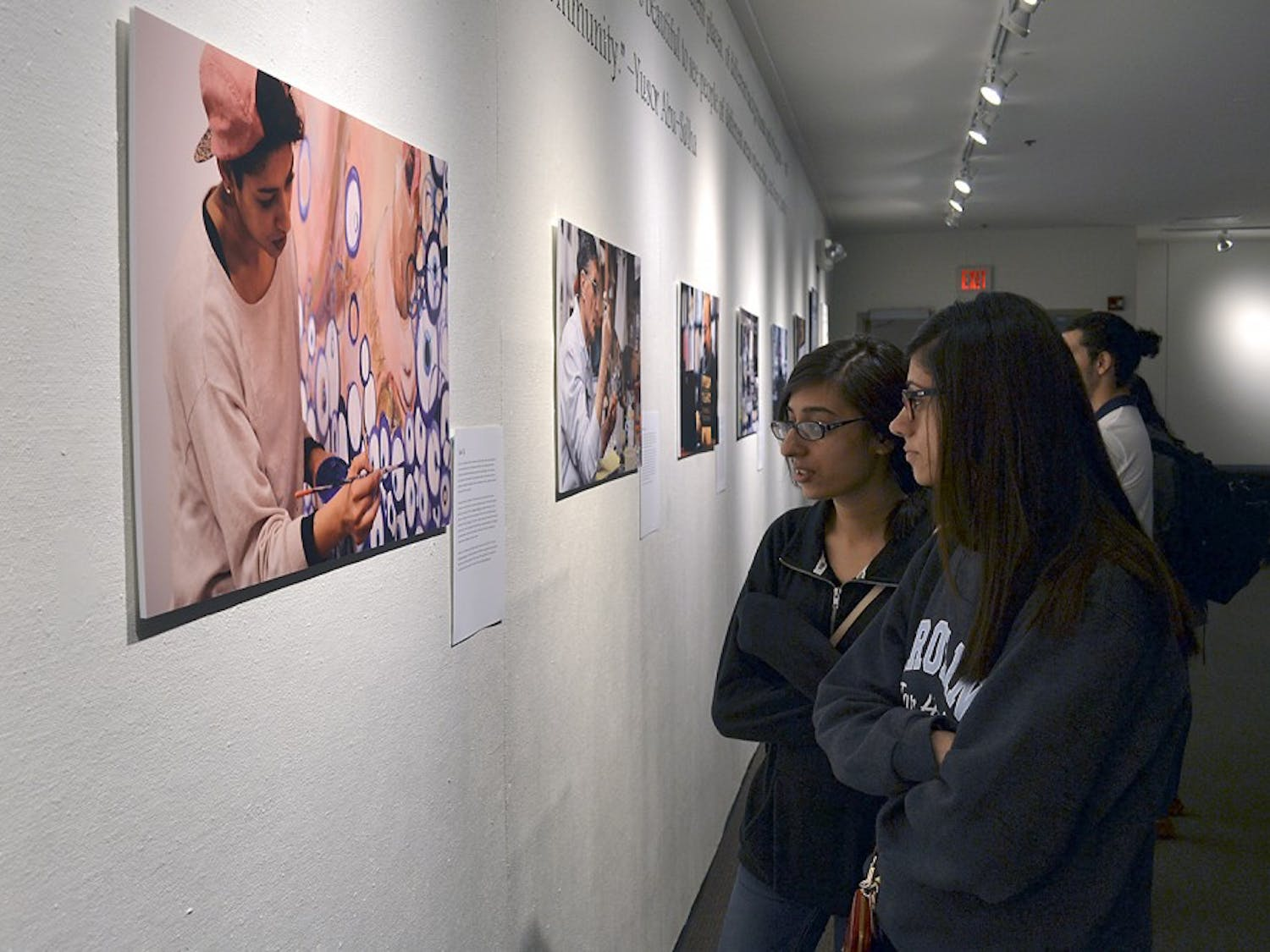 Sophomore biology majors Seher Khalid (Left), from High Point, and Noor Baloch, from Cary, display the gallery reception: Passion in Practice in the Union on Wednesday evening.