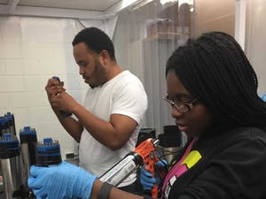 NCCU Students, Abasi Brown and Deandria Harper, working at TUNL Lab. Photo courtesy of Quiana Shepard.