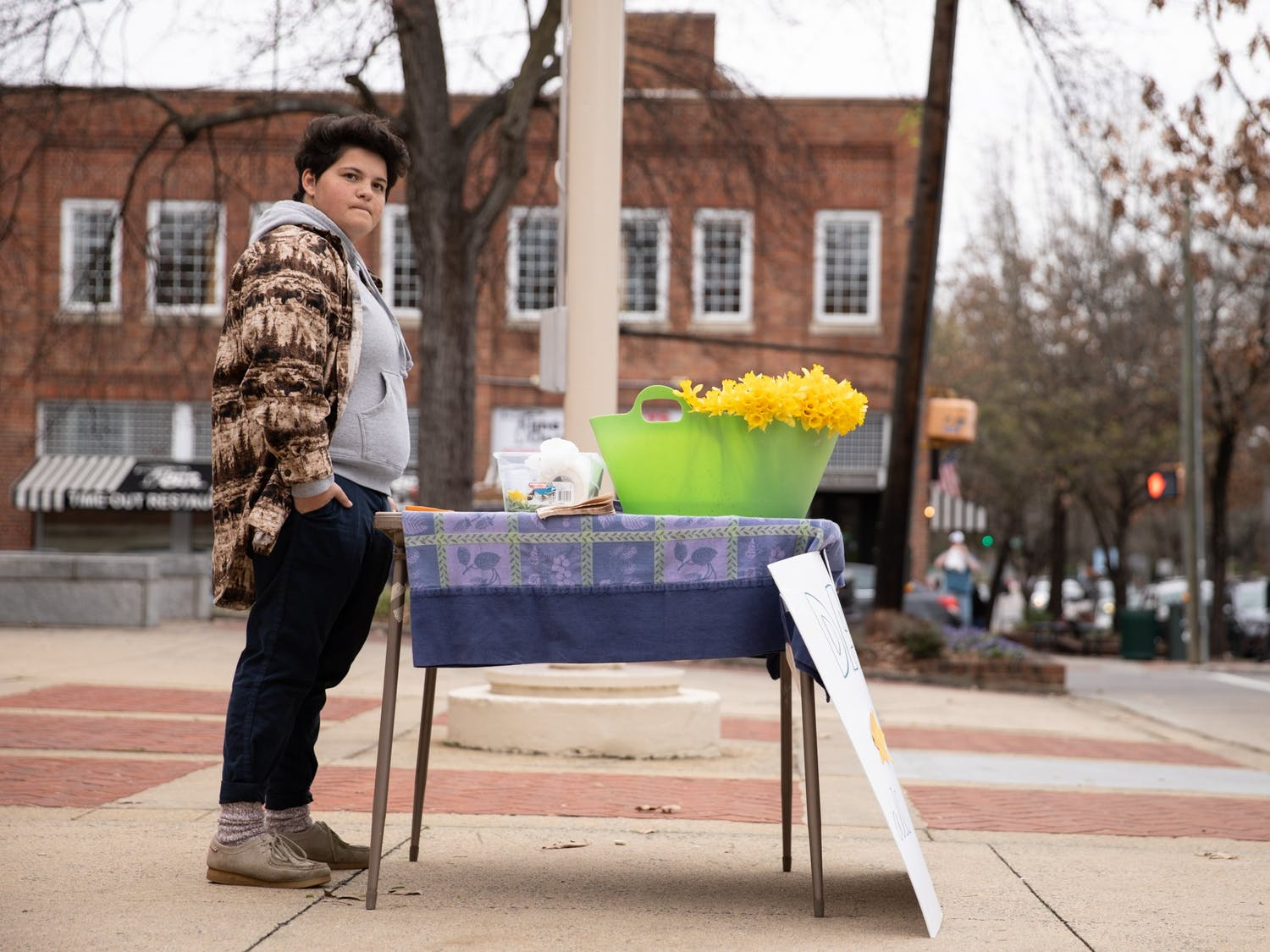 """Rebecca Mills, 18, of Chapel Hill, waits to sell a daffodil at the Peace and Justice Plaza on Sunday, Feb. 16, 2020. Mills has sold flowers from her backyard to benefit charity for 14 years. """"I feel like it's very important to help people with what you have. I have the opportunity to be able to cut all of these flowers in my backyard,"""" she said. """"I feel like it would be silly to not use that opportunity."""""""
