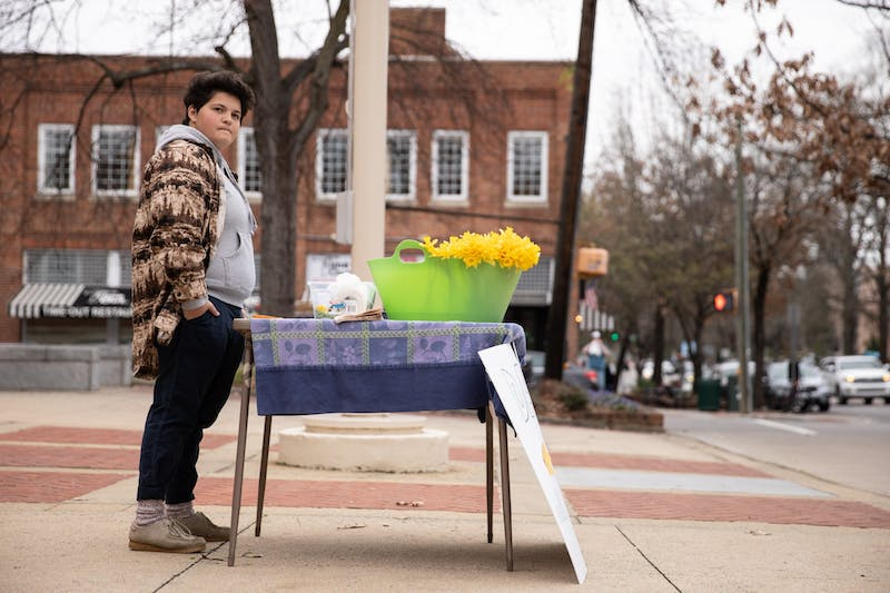 "Rebecca Mills, 18, of Chapel Hill, waits to sell a daffodil at the Peace and Justice Plaza on Sunday, Feb. 16, 2020. Mills has sold flowers from her backyard to benefit charity for 14 years. ""I feel like it's very important to help people with what you have. I have the opportunity to be able to cut all of these flowers in my backyard,"" she said. ""I feel like it would be silly to not use that opportunity."""
