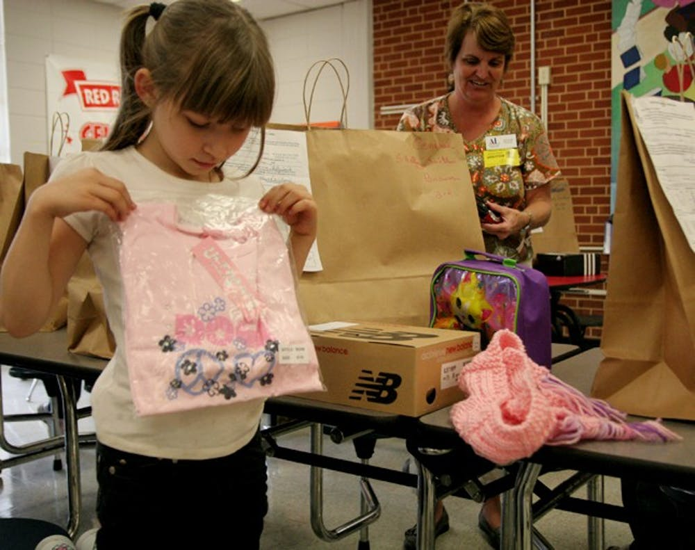 Shelly Smith,7, holds up a pink shirt she got from Operation School Bell, a program run by the Assistance League of the Triangle area.