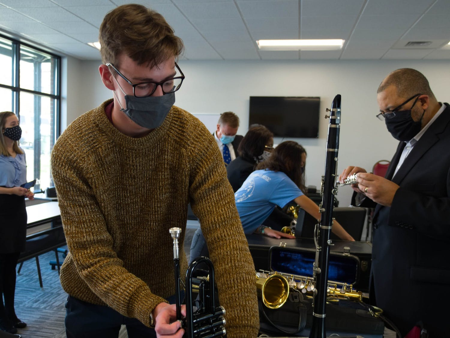Junior Luke Cain (Economics and Political Science), a volunteer at Musical Empowerment, moves a donated trumpet in the YouthWorx conference room on Wednesday, Dec. 9, 2020.