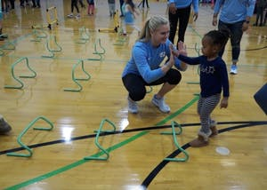UNC track and field athlete Emily Godwin high fives a participant during National Girls and Women in Sports Day, hosted at UNC.