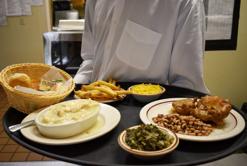 A waiter brings out a meal during lunch at Mama Dip's Kitchen on May 24.