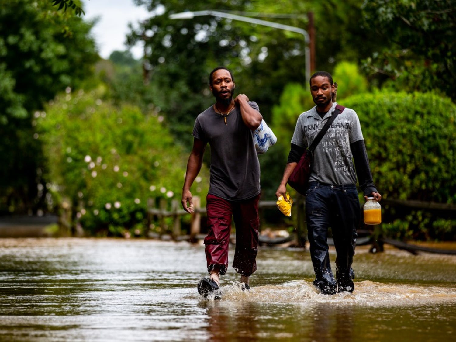"Kyrie and Michael Benton carry food and some of their waterlogged belongings through the grounds of Camelot Village apartments in Chapel Hill the morning of Sept. 17, 2018. Chapel Hill had been seemingly spared the worst of Hurricane Florence but Sunday night into Monday morning saw a downpour of heavy rain that caused flash flooding around the Triangle. Camelot Village has seen flooding in the past but never to this degree, according to Kyrie and other residents of many years. ""I lost everything in this flood,"" Kyrie said. Just as quickly as it flooded, the water began to recede late the same morning and early in the afternoon."