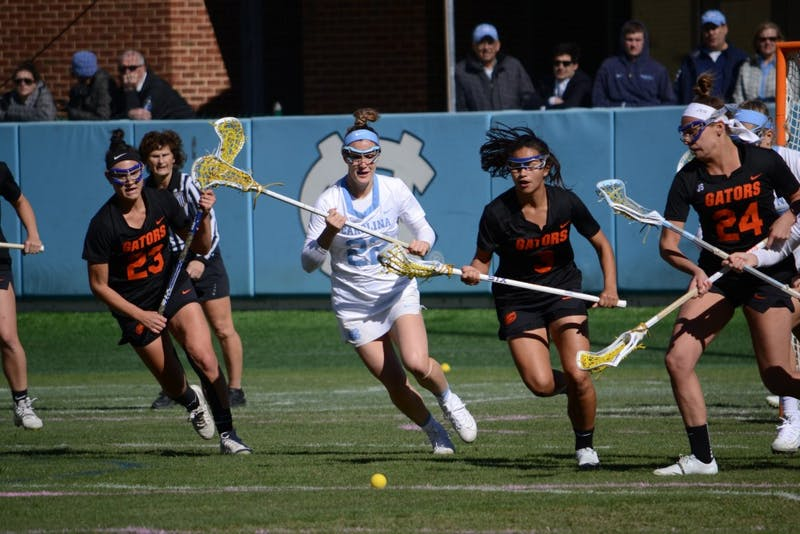 UNC junior midfielder Maggie Bill (22) fights for the ball against Florida during a game on March 3 at Kenan Stadium.