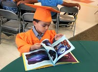 A member of the inaugural class of Book Babies turns pages in a book during the Book Babies class of 2018 graduation ceremony. Photo courtesy of Ginger Young.