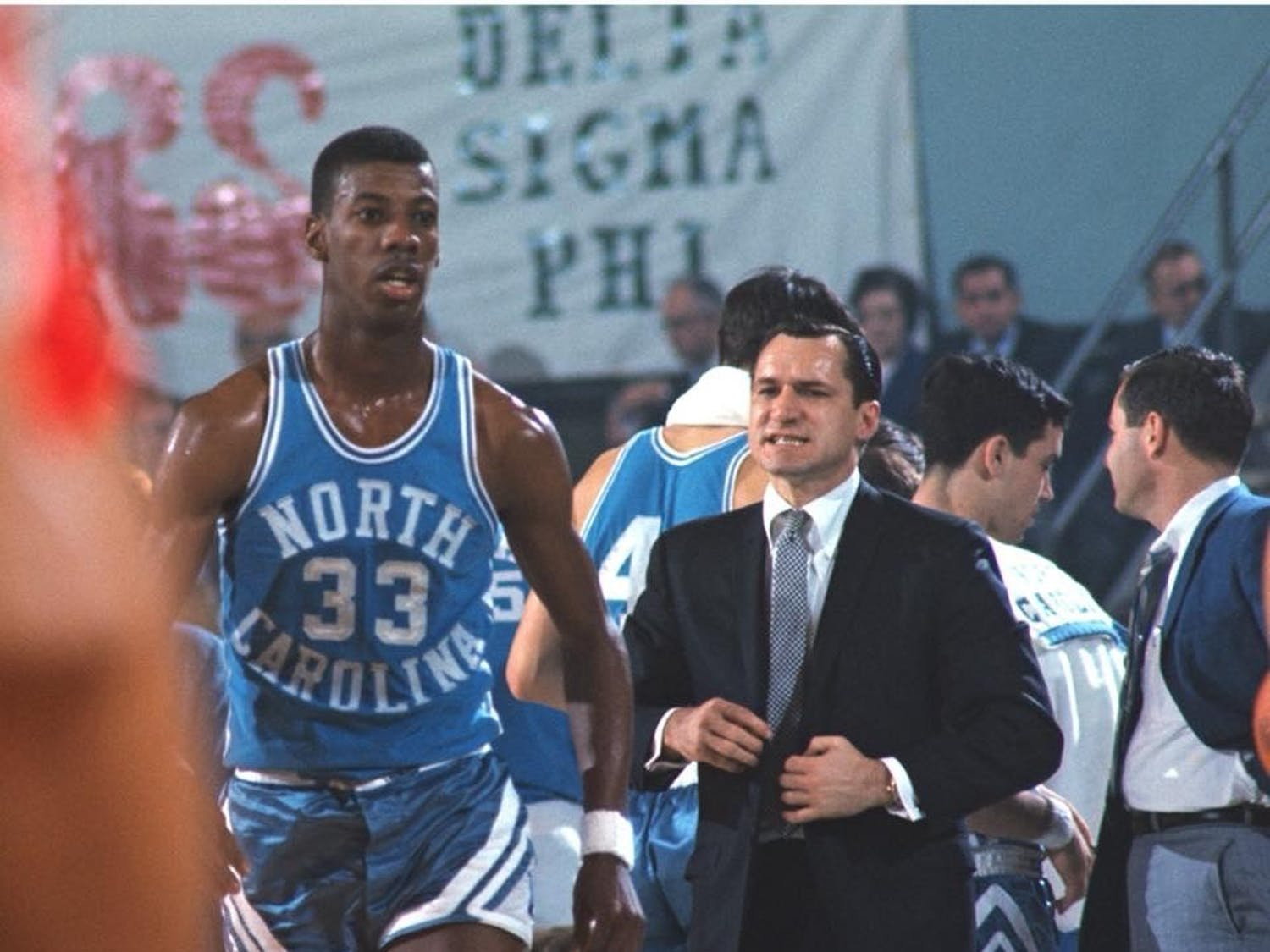 Former UNC guard Charlie Scott stands next to Dean Smith. Photo courtesy of UNC Department of Athletics.