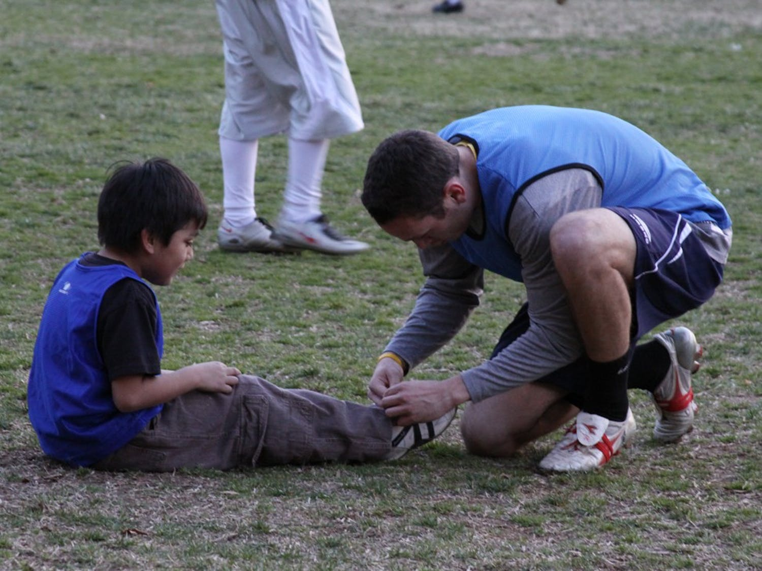 A volunteer ties the shoe laces of the youngest player Thursday evening. A number of sociology 273 students visit Abbey Court community every Thursday for a round of soccer with the local kids.