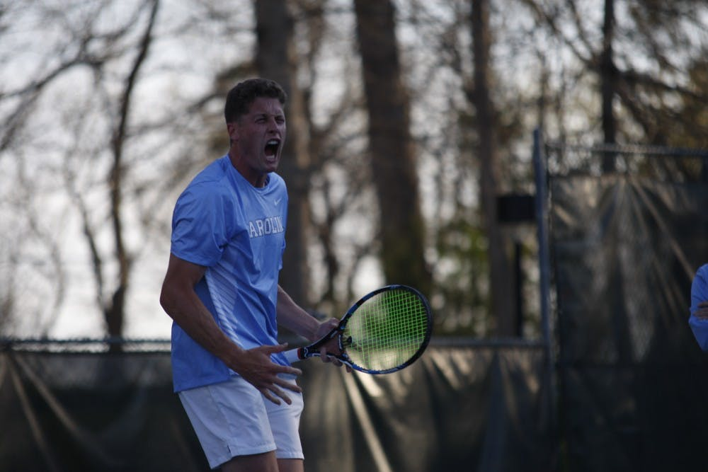 """<p>UNC men's tennis senior Blaine """"Bo"""" Boyden celebrates after winning a match during a singles set against NC State on Wednesday April 3, 2019. UNC beat NC State 4-0.&nbsp;</p>"""
