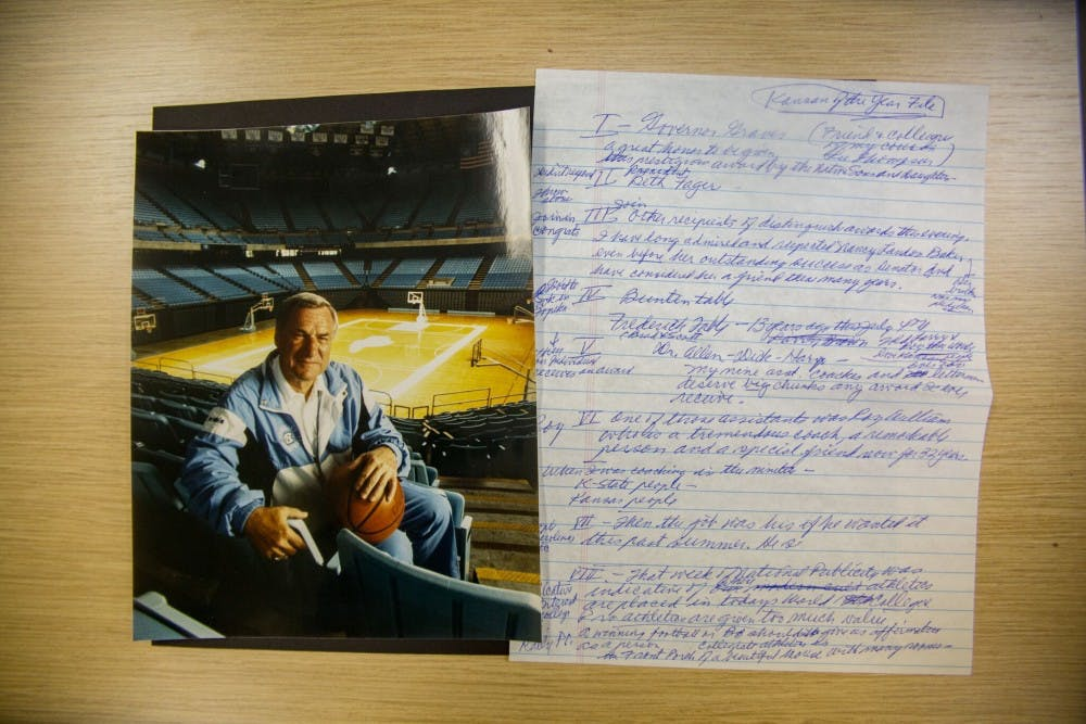 <p>A photo of Dean Smith in the Dean Smith Center rests next to hand written notes Smith wrote in preparation for his speech in 2001 after being named Kansan of the Year.</p>