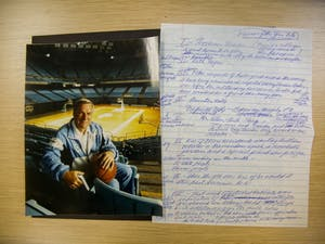 A photo of Dean Smith in the Dean Smith Center rests next to hand written notes Smith wrote in preparation for his speech in 2001 after being named Kansan of the Year.