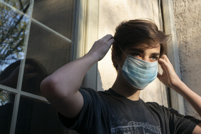 A student puts on a mask before leaving his house on Wednesday, May 20, 2020.