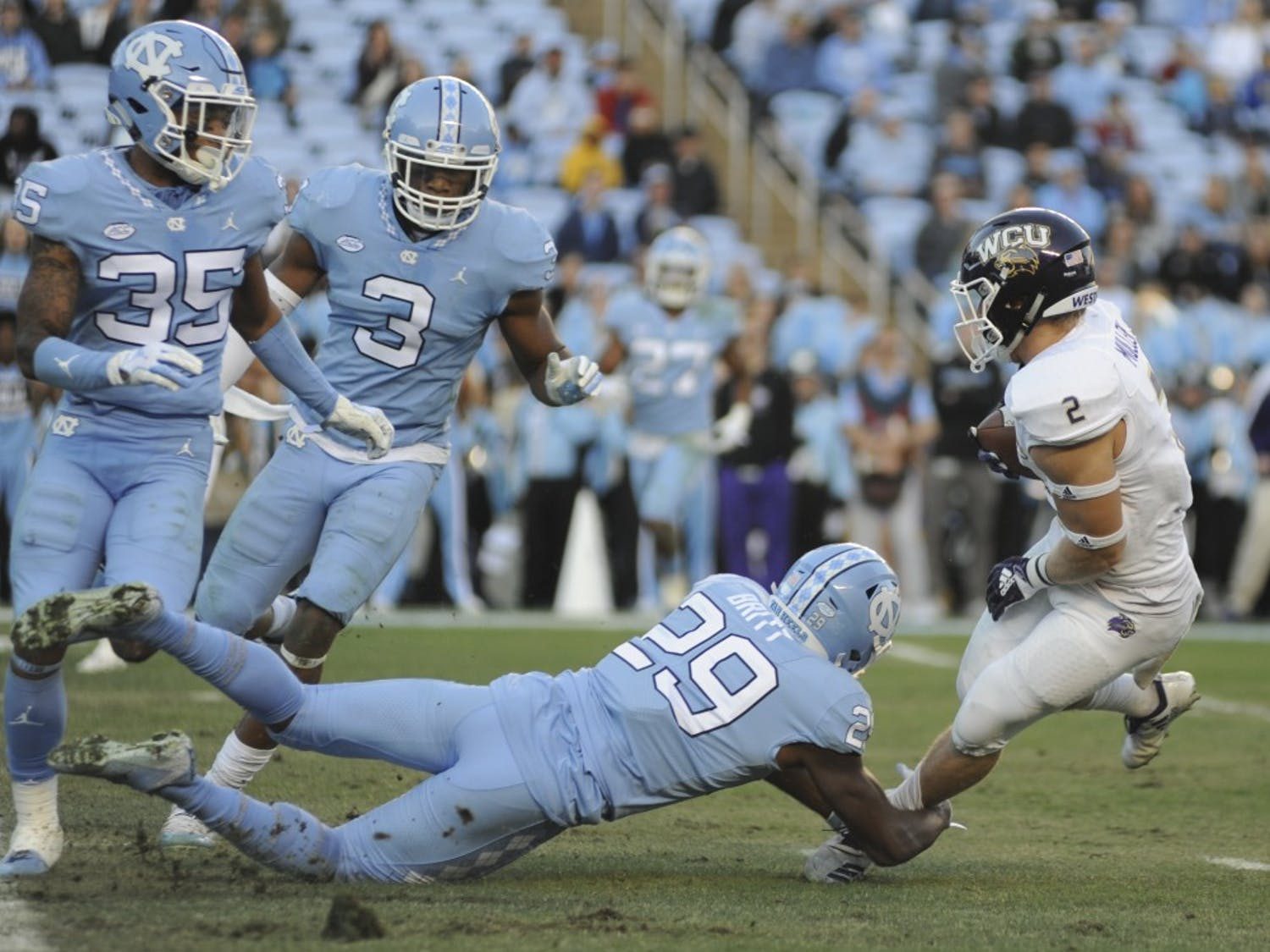 UNC senior safety J.K. Britt (29) grabs WCU redshirt junior wide receiver Nate Mullen (2) to intercept a run on Saturday, Nov. 17, 2018, in Kenan Memorial Stadium. The Tar Heels won 49-26 against Western Carolina.
