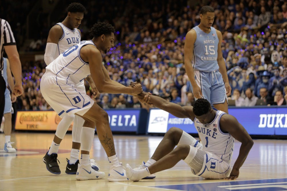 Duke center Marques Bolden (20) helps teammate Zion Williamson (1) stand up after suffering from a knee injury following a shoe malfunction.