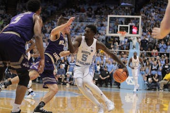 North Carolina guard Jalek Felton (5) goes behind the back on Western Carolina guard Matt Halvorsen (2) on Dec. 6 in the Smith Center.