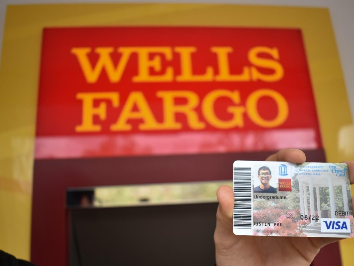 DTH Photo Illustration. UNC sophomore Justin Pau holds his Wells Fargo One Card Plus in front of the Wells Fargo ATM located next to Davis Library. The Wells Fargo One Card Plus is no longer available, and now is offering the UNC Debit Card to better protect personal information.