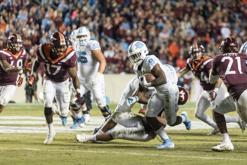 Sophomore running back Michael Carter (8) runs through a group of opposing players during the Tar Heels' 22-19 loss against Virginia Tech on the night of Saturday, October 13, 2018 in Keenan Memorial Stadium in Chapel Hill, NC.