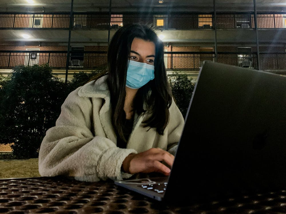 """First-year student Lorena Negron does virtual work outside of Eringhaus Residence Hall on March 8, 2021. """"While I am grateful to have the opportunity to be on campus, I know that it isn't everything it's supposed to be,"""" said Negron."""