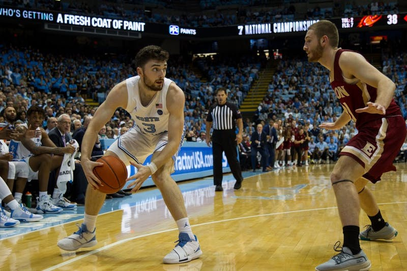 Junior guard Andrew Platek (3) keeps ball from opposing player in in basketball game against Elon University on Thursday, Nov. 20, 2019. UNC won 75-61.