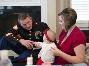 Marine Corps veteran Dac Carpenter and his wife Holly play with their daughter. An implant let Dac Carpenter regain all of the hearing in his left ear.
