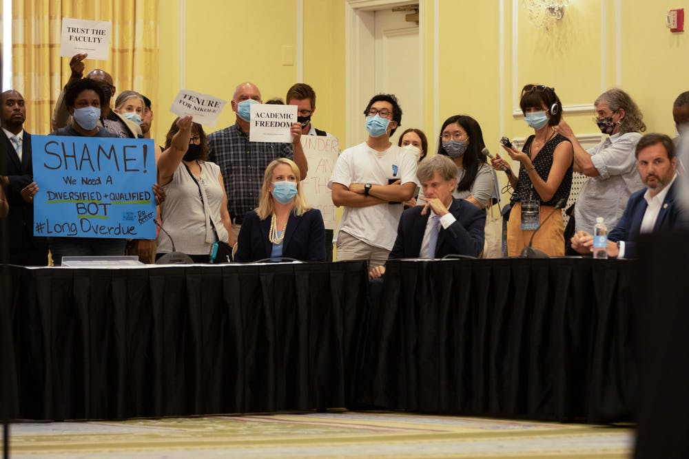 Protestors stand inside the Board of Trustees special meeting on Wednesday before the board went into closed session for the vote on Nikole Hannah-Jones' tenure.