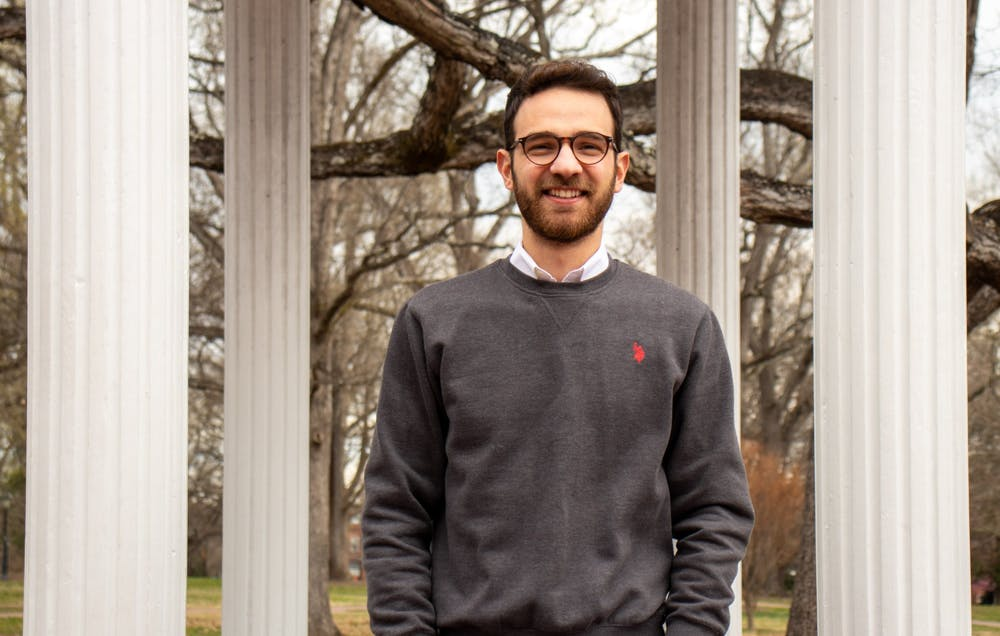 <p>Georgios Kostantinis, vice president of The First-Generation Student Association, poses for a portrait in front of the Old Well on Monday, Mar. 15, 2021.</p>