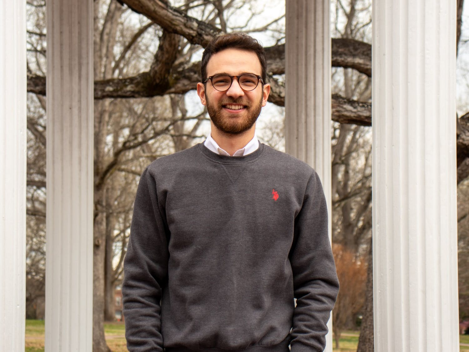 Georgios Kostantinis, vice president of The First-Generation Student Association, poses for a portrait in front of the Old Well on Monday, Mar. 15, 2021.