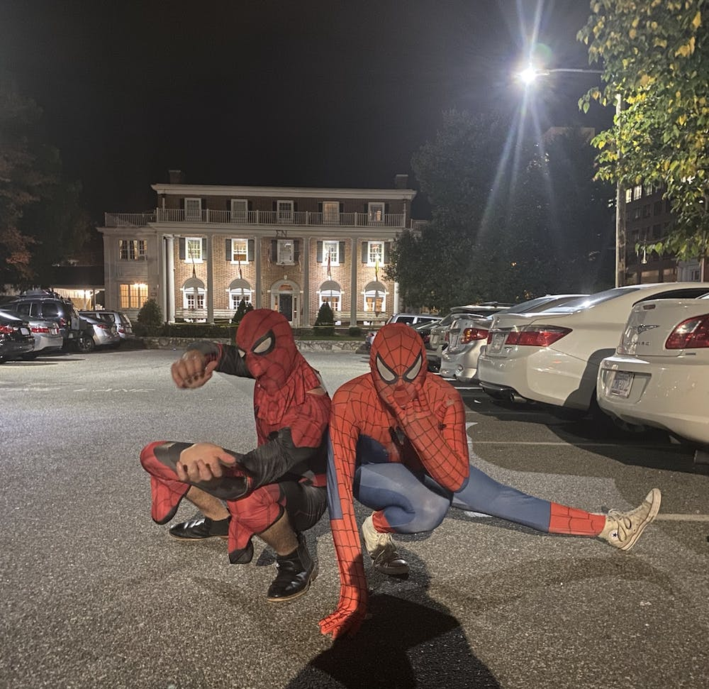 """Two of the """"Peter Parkers"""" involved in Tuesday night's Spider-Men event pose pretending to shoot webs out of their arms, as they did in campus libraries."""