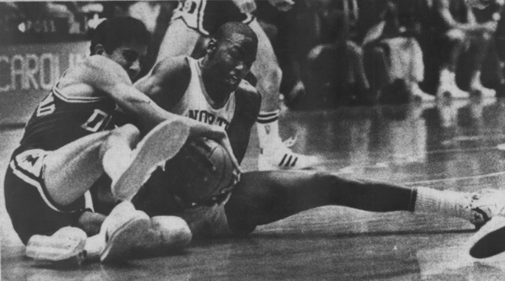 <p>DTH Archive. UNC sophomore Michael Jordan fights with Chip Engelland for possession of the ball in Jan. 22, 1983's 103-82 thrashing of Duke. Photo by Al Steele.&nbsp;</p>