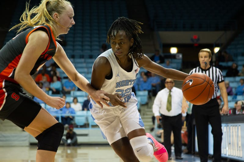 UNC senior guard Shayla Bennett (22) dribbles towards the goal while Syracuse junior forward Digna Strautmane (45) works to block during a game in Carmichael Arena on Thursday, Feb. 13, 2020. The Orange beat the Tar Heels 74-56.