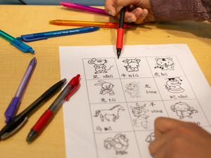 DTH Photo Illustration. A student points at an illustration of a cow accompanied by the Mandarin word on a practice worksheet in Chapel Hill, N.C., on Monday, March 18, 2019. Glenwood Elementary resolved to expand their Mandarin immersion program and phase out other tracks, prompting redistricting for current kindergarteners whose parents did not want them to participate.