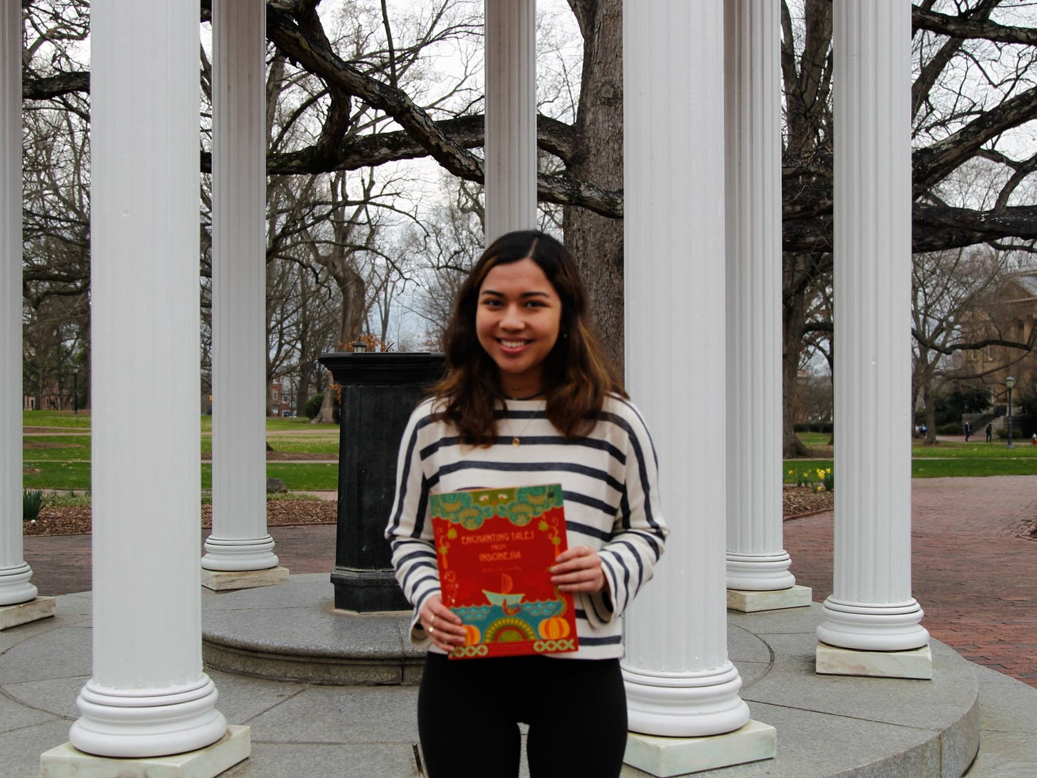 """Andari Deswandhy, a first-year global studies major, poses for a portrait at the Old Well with her book, Enchanting Tales from Indonesia, on Feb. 26, 2020.  Deswandhy says, """"I'm passionate about bringing different cultures together and helping people find similarities in our differences.""""."""