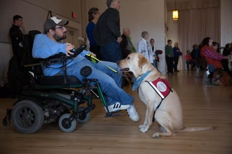 A service dog looks at its owner as two dogs graduate the Eyes Ears Nose and Paws program.