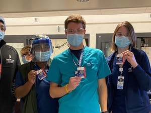 Hospital workers pose with their kits and badges. Photo courtesy of Noam Brenner.