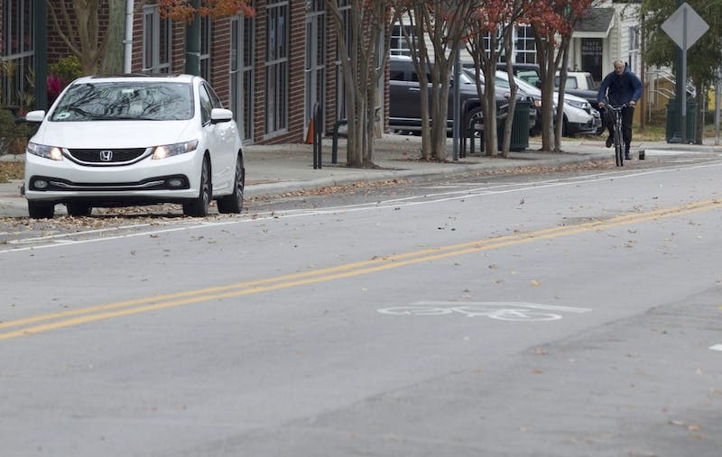 Biker rides down Rosemary St. in Chapel Hill, Monday, Nov. 26,  2018.  Chapel Hill is implementing bollards, dividers to deter cars from using bike lanes like the white car shown on the left.