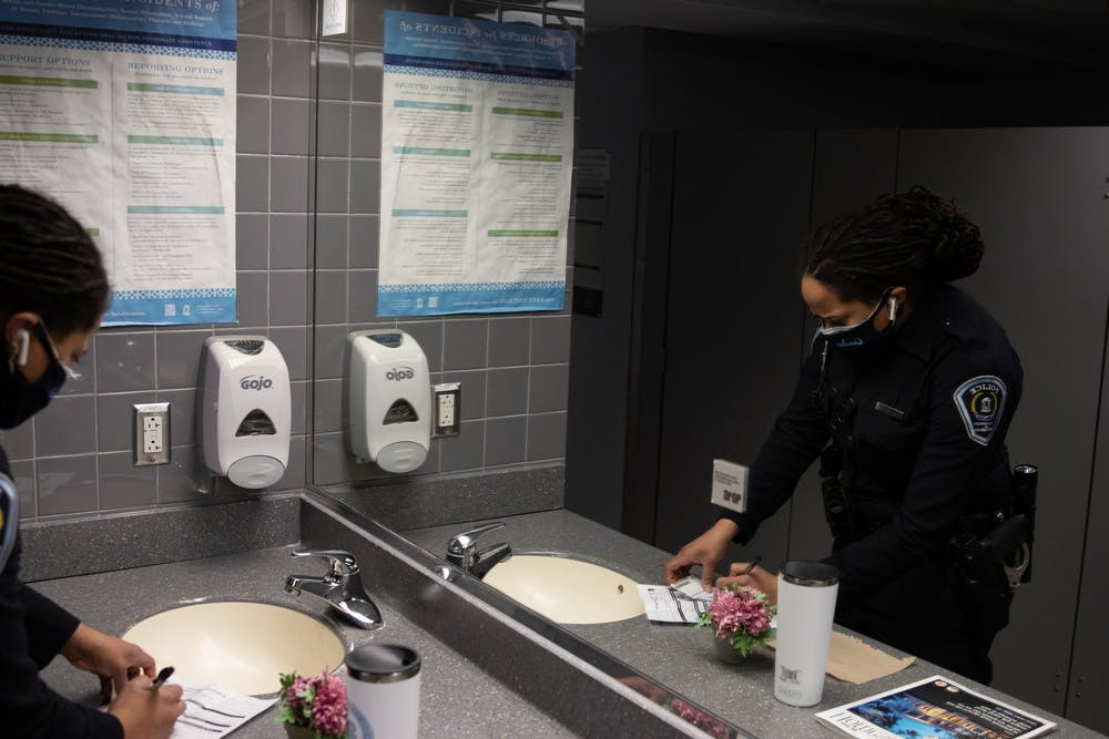 UNC Police Officer McCray examines a display left by a vandal at the Campus Y on Jan. 25, 2021. The Campus Y was vandalized sometime during the weekend of Jan. 23-24.