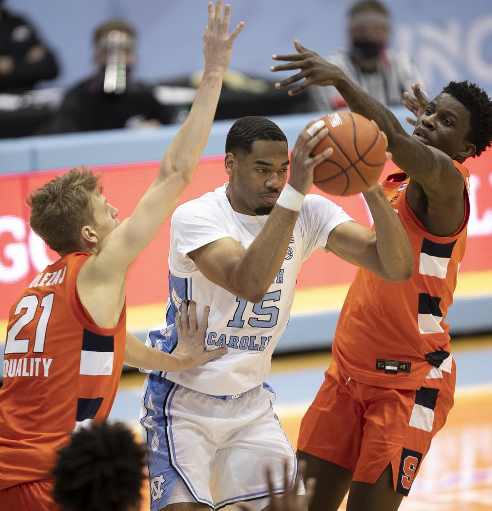 <p>North Carolina's Garrison Brooks (15) is trapped by Syracuse's Marek Dolezaj (21) and Kadary Richmond (3) during the second half on Tuesday, January 12, 2021 at the Smith Center in Chapel Hill, NC. Photo courtesy of Robert Willett.</p>