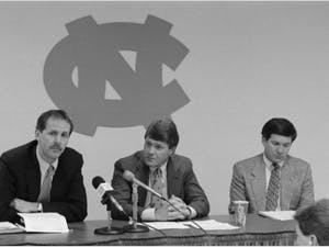 Press Conference, WCHL 1360. (Left to right): Unidentified man, UNC Athletic Director John Swofford, UNC Head Football Coach Mack Brown. In the Hugh Morton Photographs and Films #P0081, copyright, 1988-1994, North Carolina Collection, University of North Carolina at Chapel Hill Library.