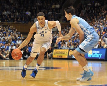 Forward Jayson Tatum (0) dribbles around sophomore forward Luke Maye (32) on Feb. 9. The Tar Heels take on the Blue Devils again on Saturday.
