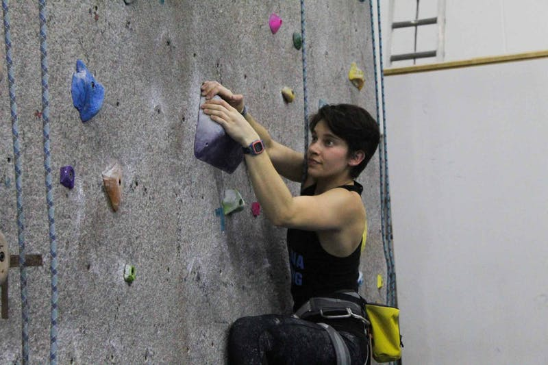 """Marisa Alam, a sophomore human development and family studies major, demonstrates a rock climbing technique during Rock Climbing Club practice on Thursday, Feb. 27, 2020 at Fetzer Gym C. """"Everyone in th climbing community is super chill, no matter your skill level, it's just a happy place to be"""" she said."""
