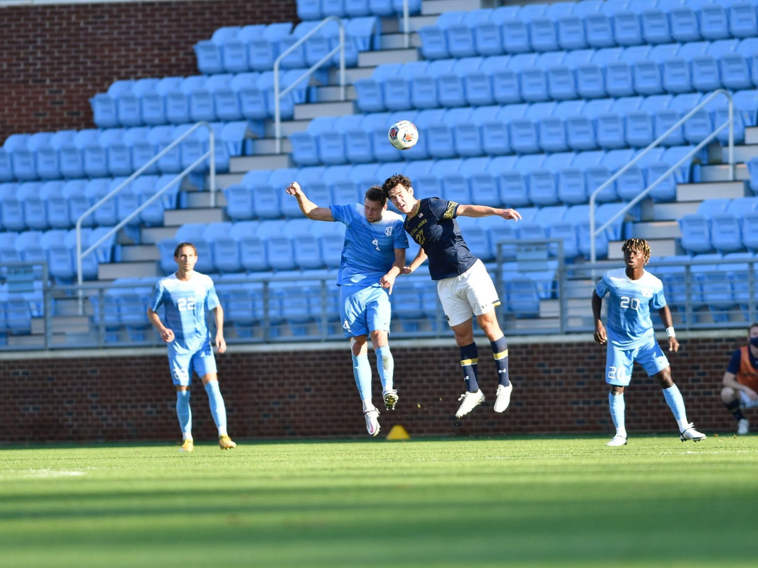 UNC's graduate defender Joe Pickering (4) goes up for a header against Notre Dame's junior forward Jack Lynn (27) during the first round of the ACC tournament in Dorrance Field on Sunday, Nov. 15, 2020. UNC fell to Notre Dame 1-0. Photo courtesy of Dana Gentry for UNC Athletic Communications.