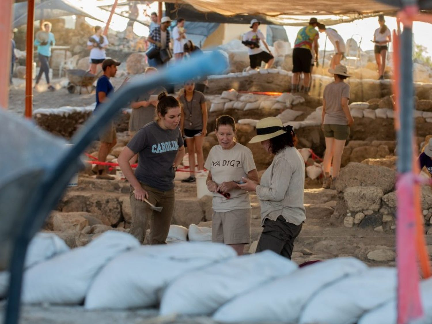 (From left to right) Jocelyn Burney, Magness and Shua Kisilevitz discuss strategy at the excavation site in Huqoq, Israel. (Photo by Will Melfi)