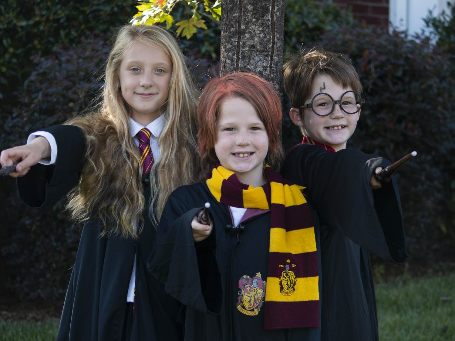 From left to right: Amelia, eight and a half, Evan, nine, and Will, nine, point their wands in preparation for Halloween night in Durham on Thursday, Oct. 22, 2020. Amelia lives across the street from Evan and Will, who are identical twins and just five and a half months older than Amelia. The three, who have all known each other their whole lives, will be going as Harry, Hermione and Ron from Harry Potter. They all agreed that they are most excited to get candy and play corn hole on Halloween.