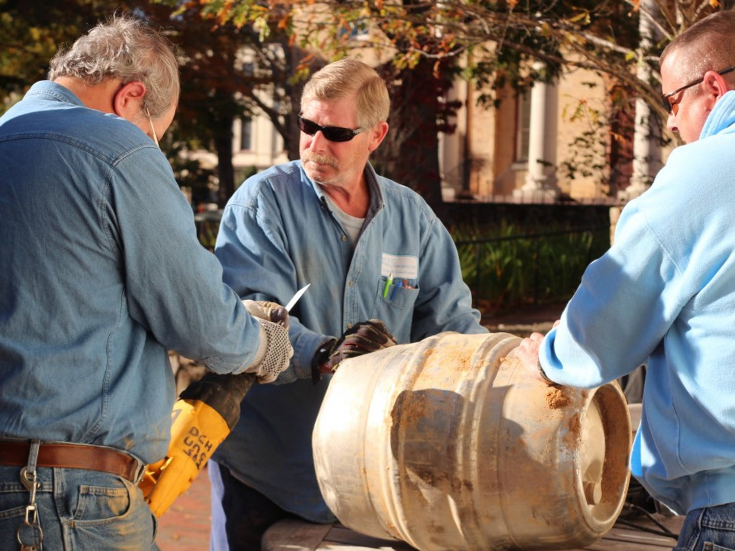The graduating class of 1988 returned to campus to recover the time capsule they buried a quarter of a century earlier. The time capsule, a stainless steel keg donated by a then local bar, proved to be a challenge for the grounds workers that had to both dig it up and cut through it on Friday at 1 p.m. The keg was buried under a plaque on Polk Place between the flagpole and  South Building. The alumnae will be celebrating their 25th reunion during Homecoming weekend and look forward to exploring the capsule's artifacts in Wilson Library this week.