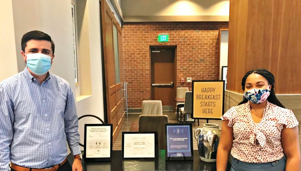 <p>Donald Strickland and Martina Brooks at the Carrboro Hampton Inn &amp; Suites inspect safe breakfast procedures. Photo Courtesy of Laurie Paolicelli.</p>