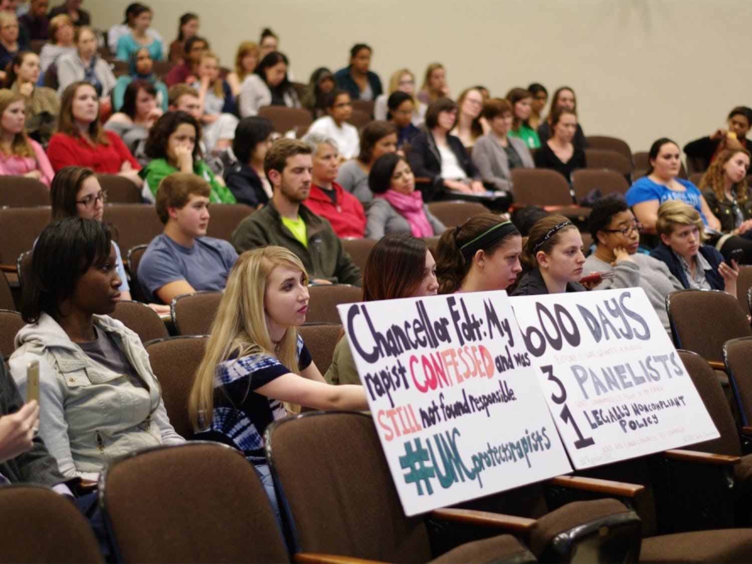 "Junior Landi Gambill holds a sign addressing Carol Folt in the screening of the documentary ""The Hunting Ground"" in the Carroll Hall auditorium on Thursday."