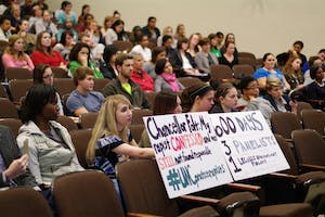 """Student and advocate Landen Gambill holds a sign addressing Carol Folt in the screening of the documentary """"The Hunting Ground"""" in the Carroll Hall auditorium on Thursday."""