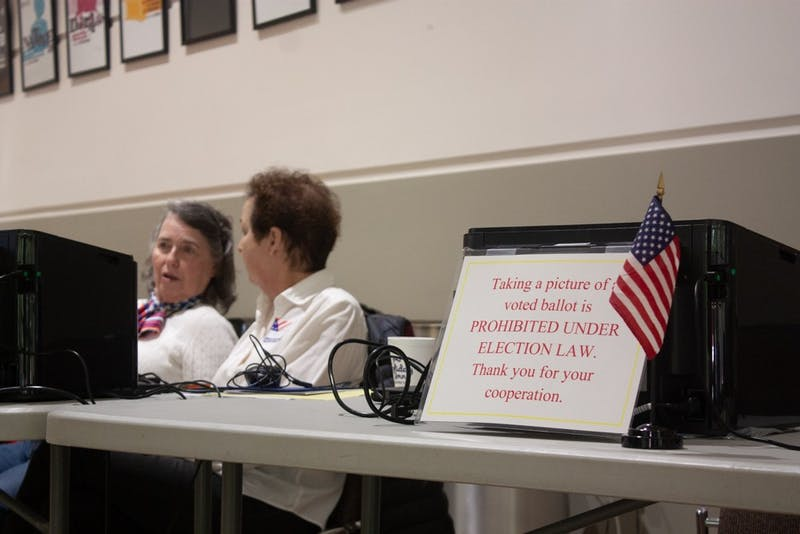 Country Club precinct's Chief Judge Carol Hazard and Democratic representative Barbara Wendell work the check-in table at the Paul Green Theatre on Tuesday, Nov. 5, 2019.