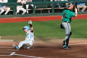 North Carolina designated hitter Adam Pate (2) slides into home for one of his three runs Tuesday.